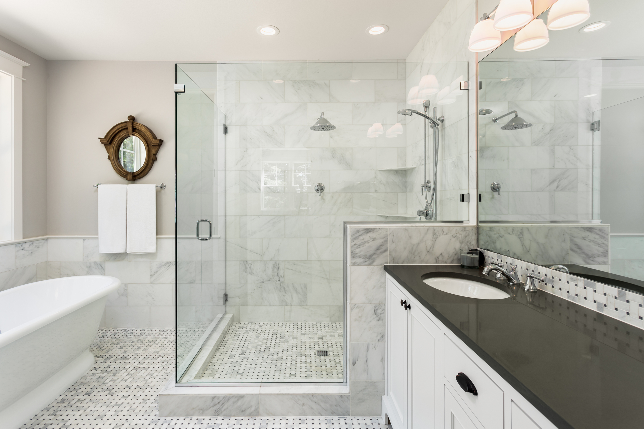 Beautiful master bathroom with shower, bathtub, and sink,  with high end furnishings, lights on